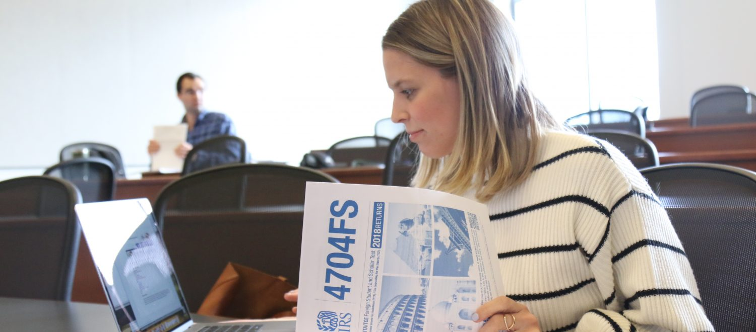 A law student enrolled in the tax clinic looks through tax forms to prepare for class.