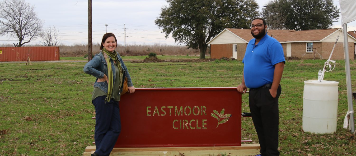 Housing Clinic Director Desiree Hensley and law student Brandon Wilson stand with the Eastmoor Circle sign.